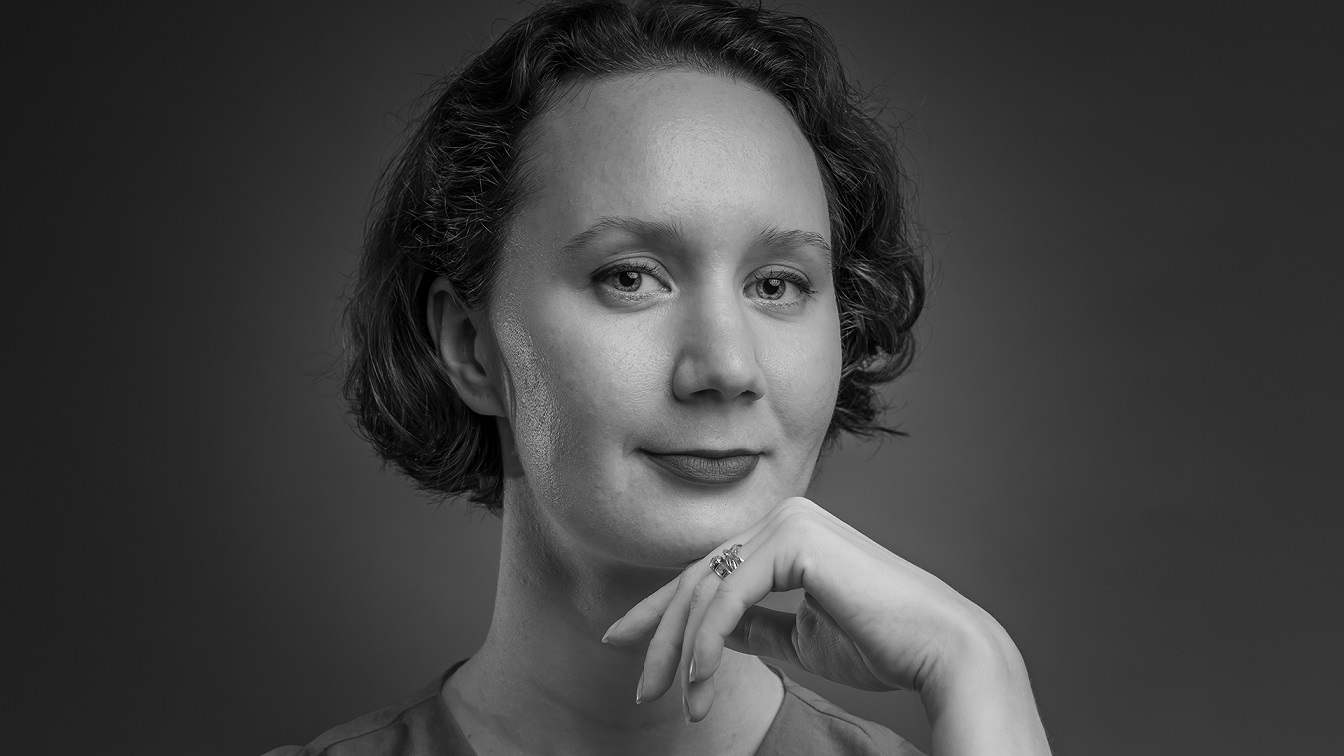 Black and white indoor studio portrait of a person posing