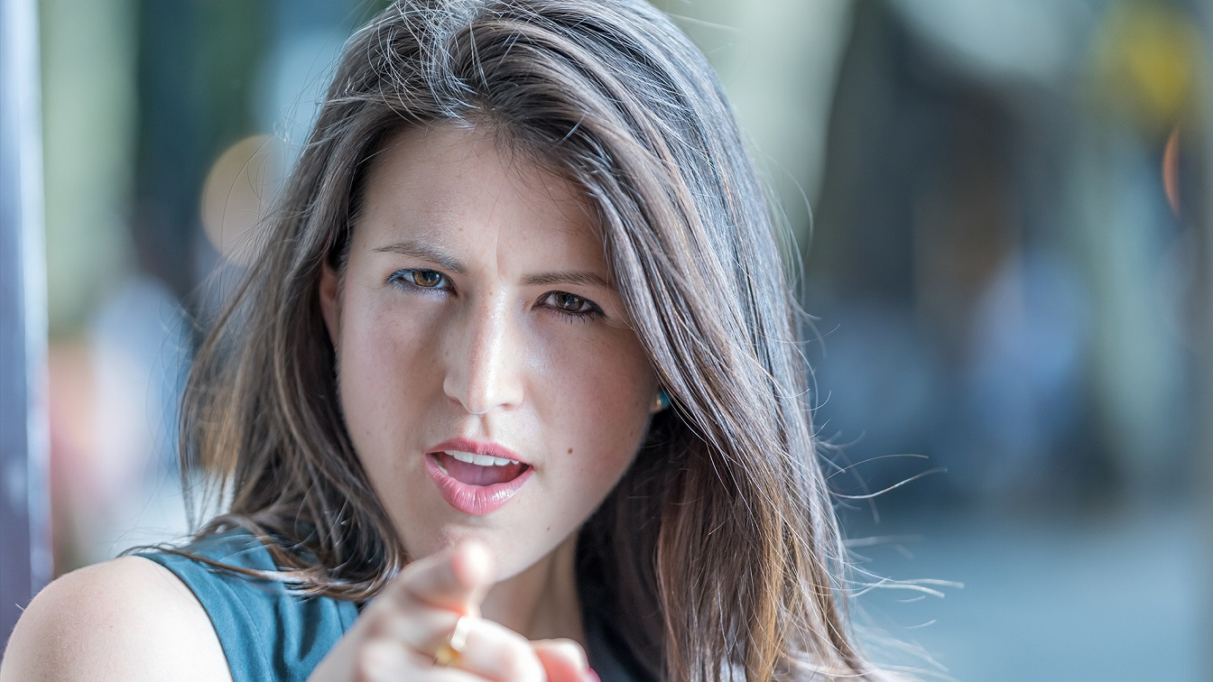 Environmental portrait of a person pointing at the camera